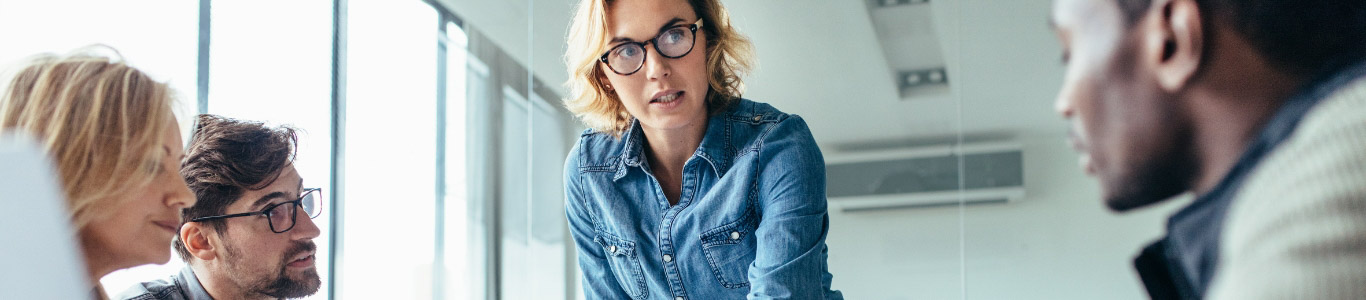 standing woman with glasses in office setting talking to co-workers that are sitting